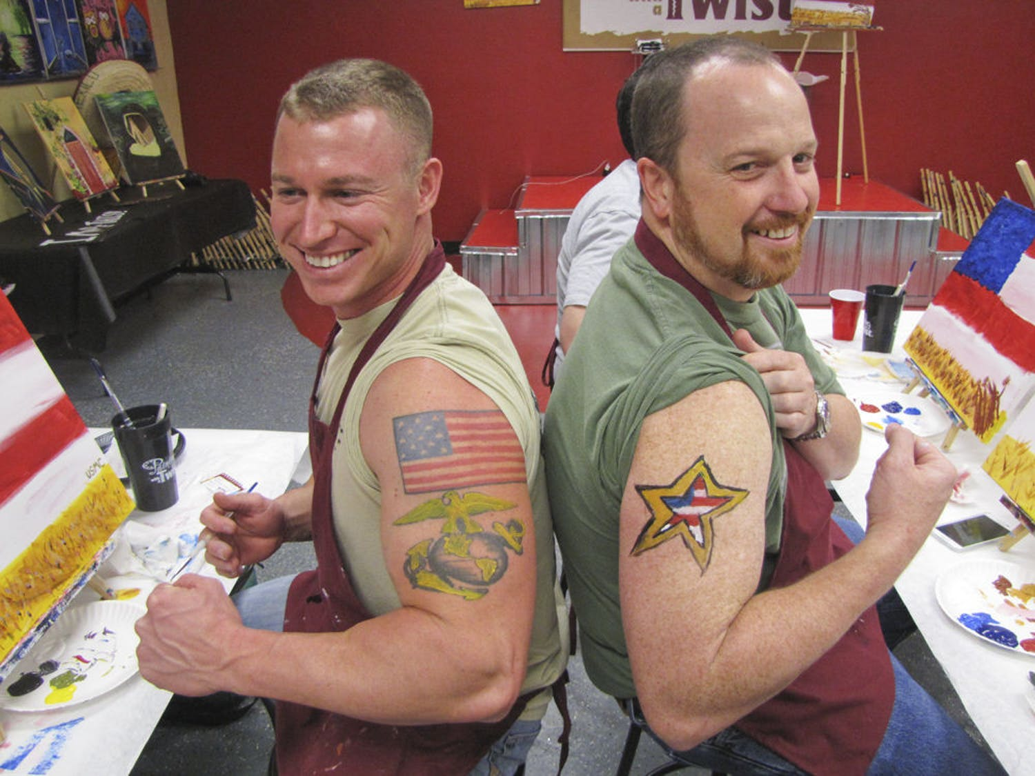 Marine Corps veteran Jacob Dodd, 29, and Army veteran Greg Revels, 43, pose with their painted tattoos Tuesday afternoon at Painting with a Twist's Veterans Day event.