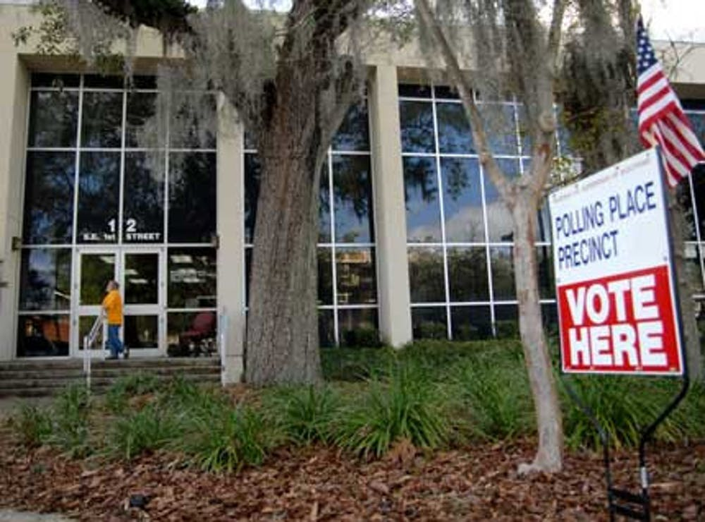 <p>Poll deputy Joseph Antonelli waits to greet early voters in front of the County Administration Building in downtown Gainesville on Thursday.</p>