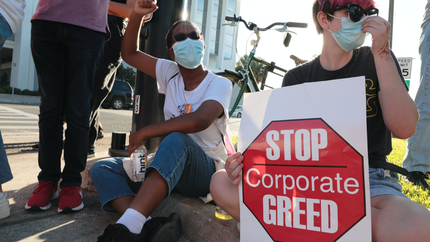Lea Guthrie (left) and Izzy Myers (right) sit in front of The Collier Companies building during the Protest for Tenant Discrimination on Thursday, Oct. 21, 2021.