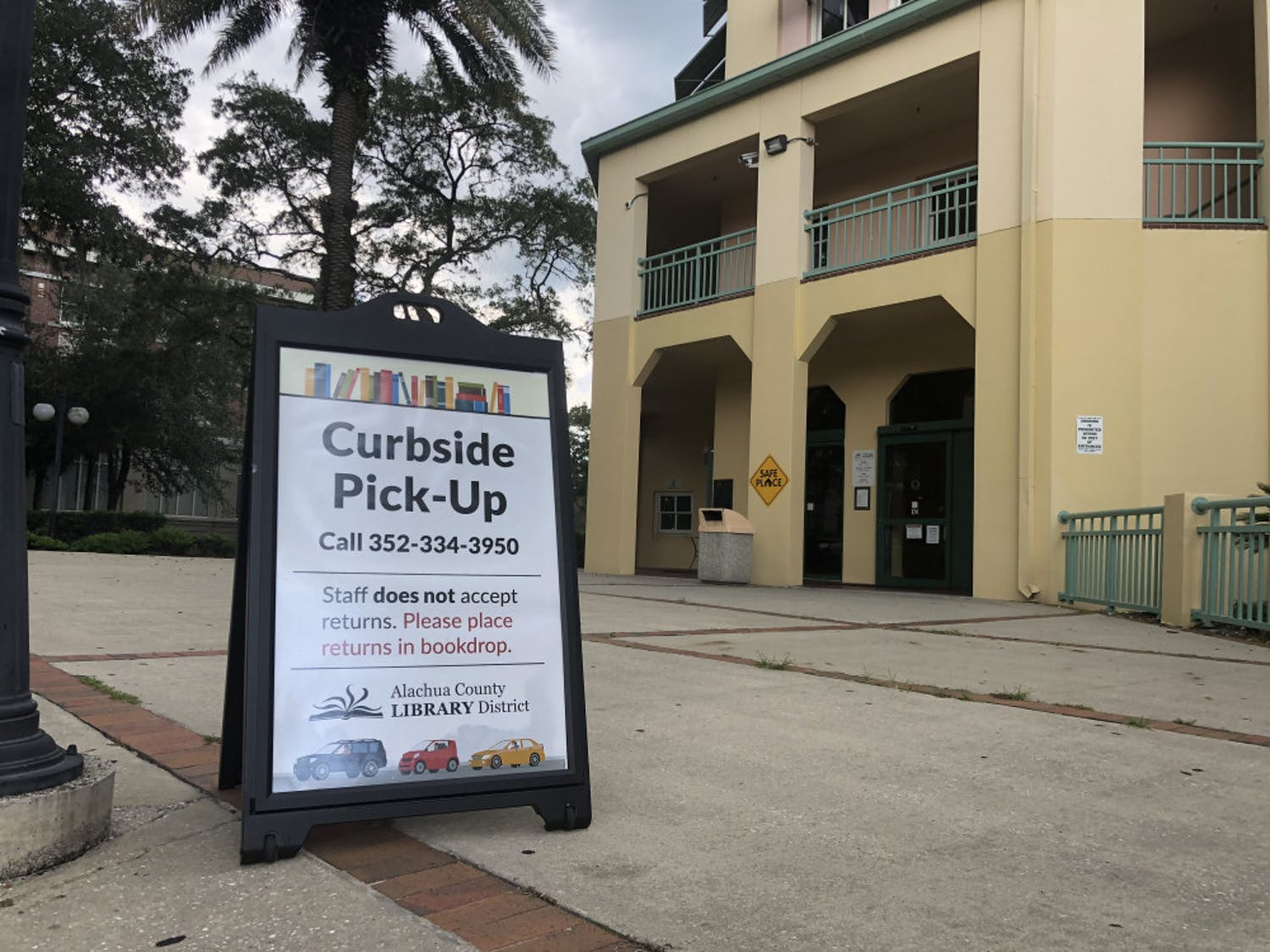Signs outside of the Headquarters Branch of the Alachua County Library District direct patrons interested in curbside service.