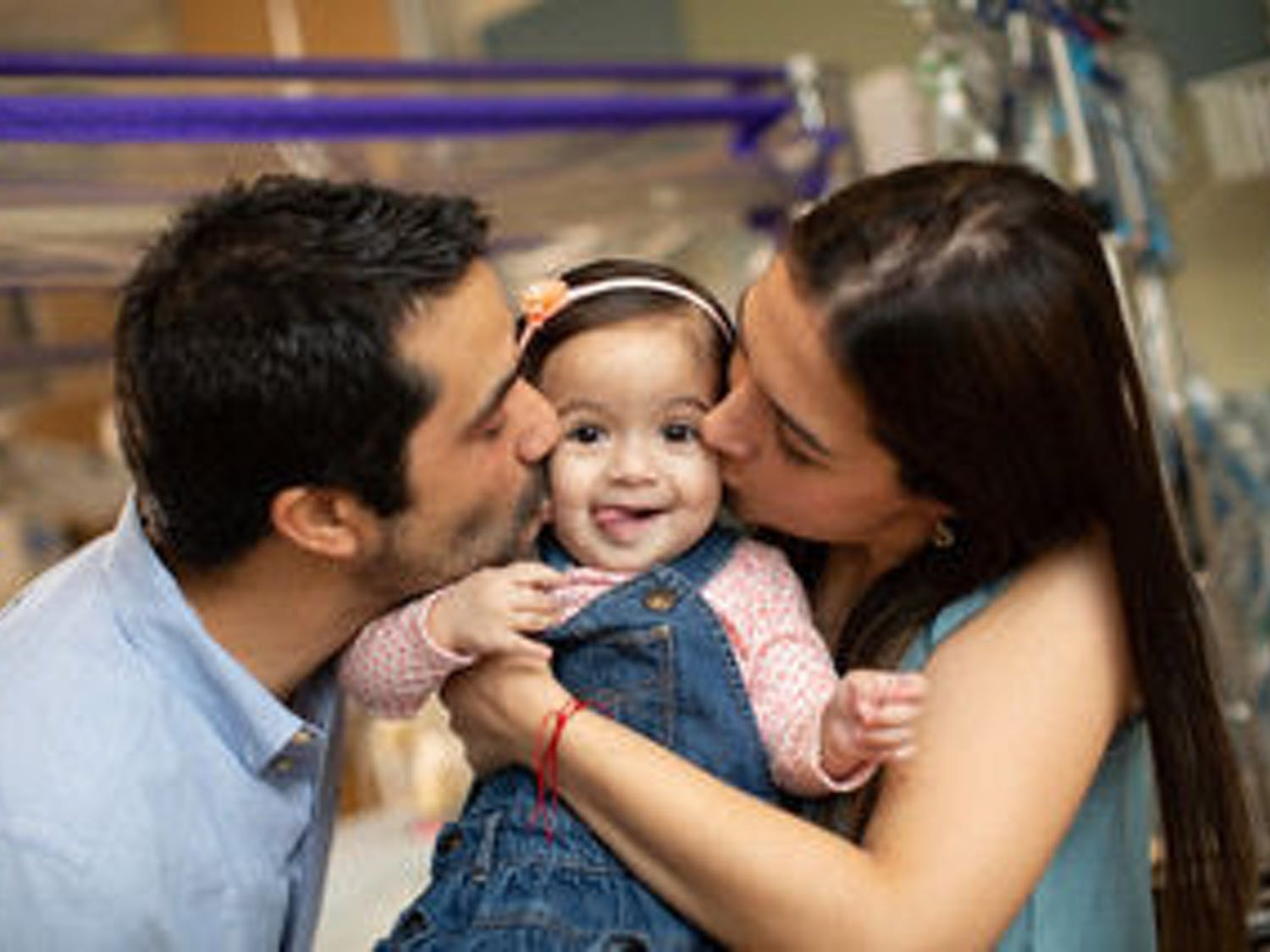 Carlos Ocampo, left, and Victoria Escobar, right, kiss their 1-year-old Valeria Ocampo, who was released from UF Health Shands hospital last Friday.