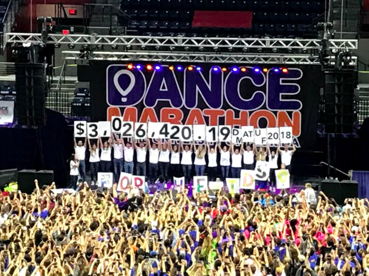 UF Dance Marathon staff members hold signs revealing the total amount of money fundraised this year, totaling $3,026,420.19 for the Children's Miracle Network.