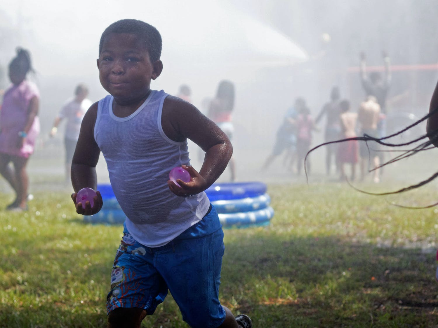 "Ja'Keil Norris, 5, runs away from the firetruck hose while carrying two water balloons Saturday during Beat the Heat Water Day. The event featured kids-versus-cops water balloon battles along with blasts of water from the deck gun of a fire truck, which was advertised as ""the world's largest sprinkler"". Firefighters atop the firetruck would spray water over the children about every ten minutes."