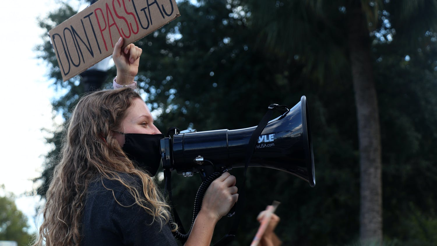 """Makenzie Griffin, 22, UF zoology senior, holds a """"Don't Pass Gas"""" sign in protest of UF's power plant construction during a rally at the corner of University Avenue and 13th Street on Friday, Sept. 24, 2021.  Griffin is an organizer with the Sunrise Movement, which planned the rally."""