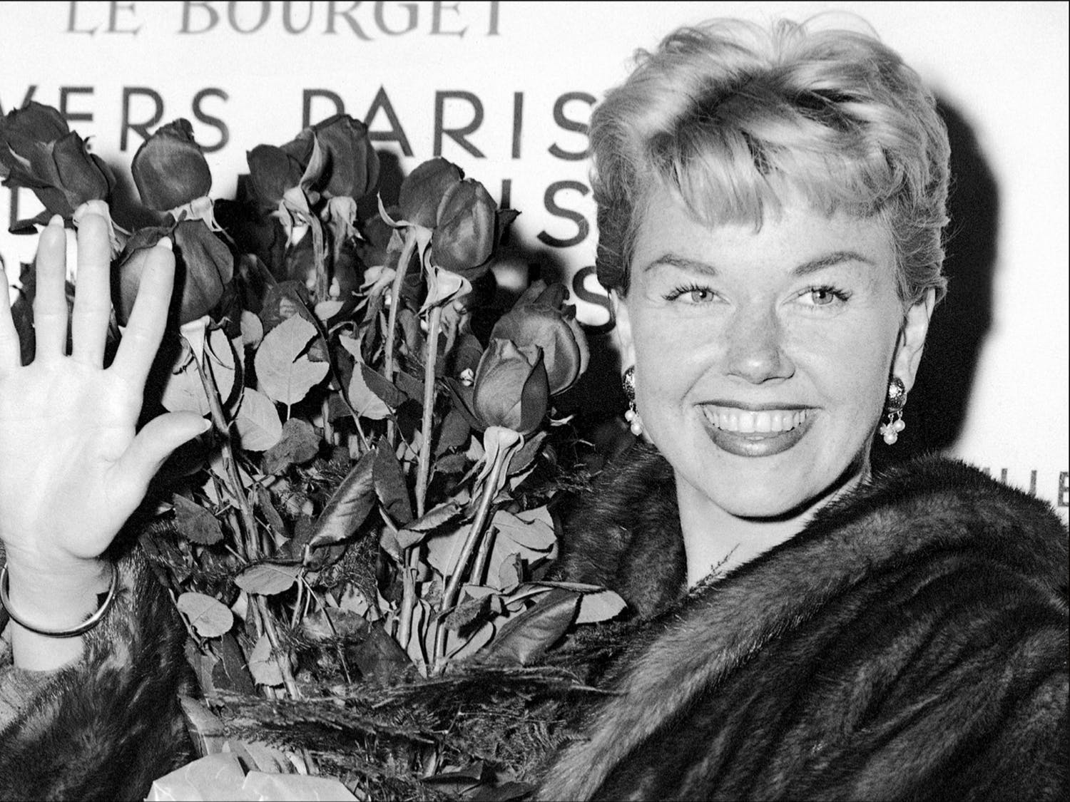In this April 15, 1955, file photo, American actress and singer Doris Day holds a bouquet of roses at Le Bourget Airport in Paris after flying in from London. The Doris Day Animal Foundation confirmed Day died early Monday, May 13, 2019, at her home in Carmel Valley, Calif. She was 97.