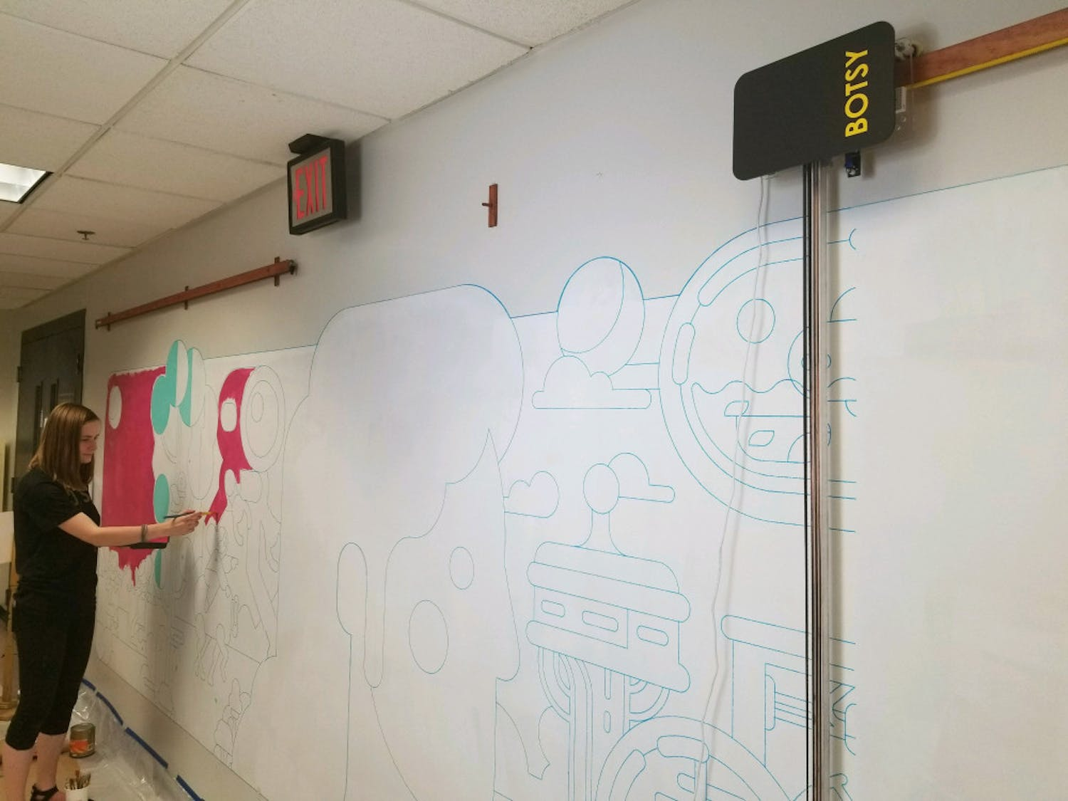 While her robot, Botsy, continues to outline the remaining pieces of a new mural on a once blank hallway in UF's New Engineering Building, UF alumna Liza Kholodkova begins to paint.