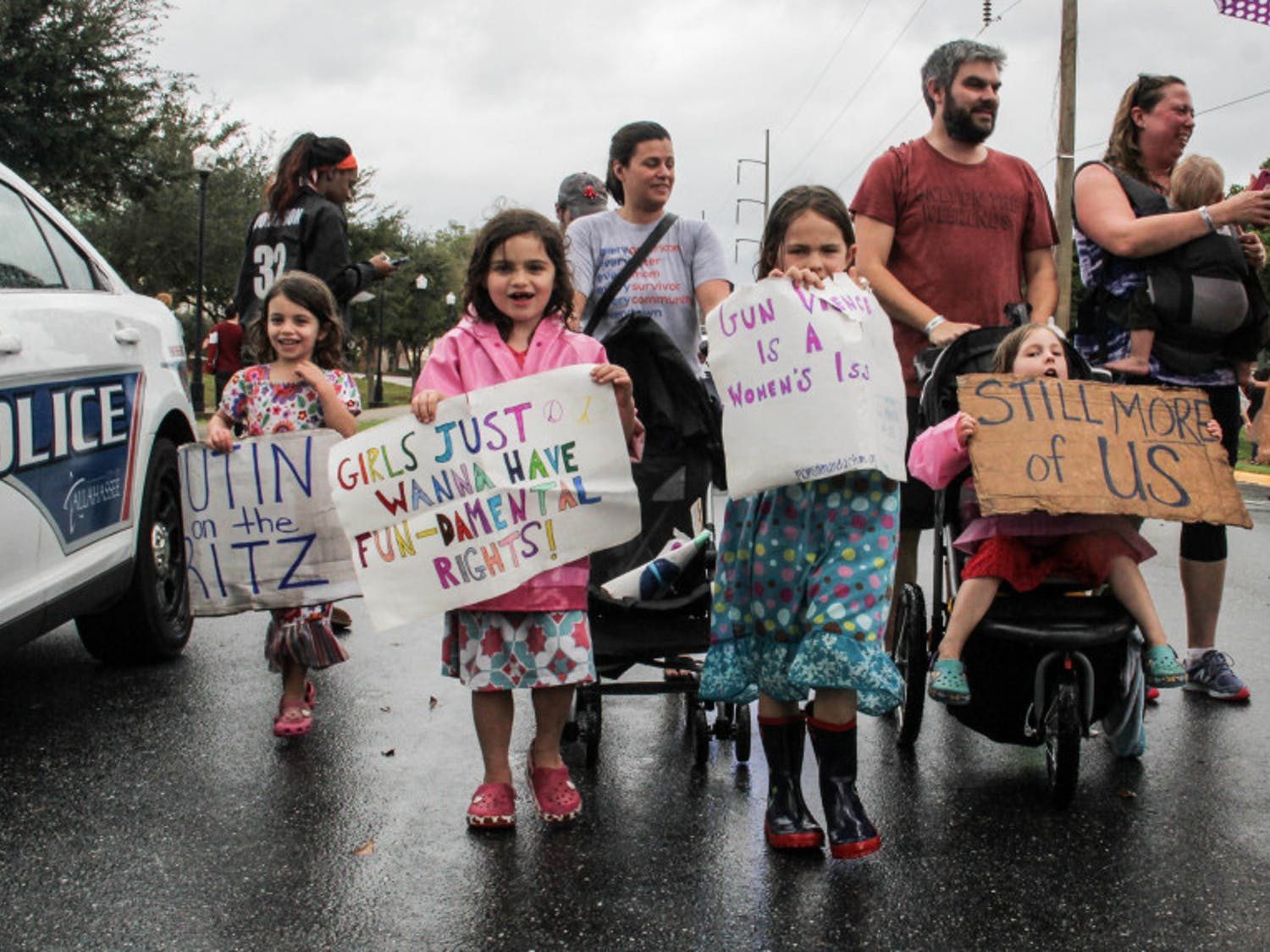 """More than 15,000protestors braved sporadic pouring rain to show their opposition to President Donald Trump in Tallahassee on Saturday. They marched a mile behind a banner reading """"All families deserve justice and security."""""""