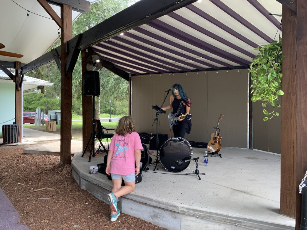 <p>Musician Camie Maree plays on stage at One Love Cafe and interacts with ayoung fan.</p>