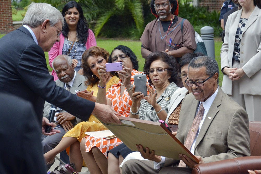 <p>Judge Stephan P. Mickle, the first African-American to get a bachelor's degree from UF and the second to graduate from UF's Levin College of Law, smiles as he receives a plaque from George Dawson, the law school's interim dean, during a tree dedication ceremony in 2015. About 75 people attended the ceremony on the UF Law West Courtyard.</p>