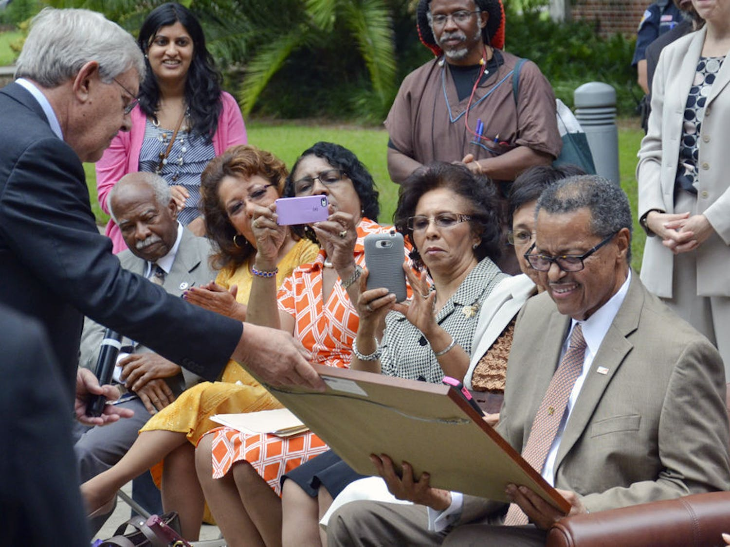 Judge Stephan P. Mickle, the first African-American to get a bachelor's degree from UF and the second to graduate from UF's Levin College of Law, smiles as he receives a plaque from George Dawson, the law school's interim dean, during a tree dedication ceremony in 2015. About 75 people attended the ceremony on the UF Law West Courtyard.