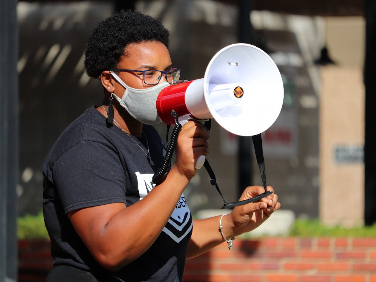 Kiara Laurent speaks to the crowd at Bo Diddley Plaza in Gainesville before protesters march to the Alachua County Courthouse on Saturday, Sept. 26, 2020. Laurent is a member of the Dream Defenders, a black-led organization of young people who planned this event. (Lauren Witte/Alligator Staff)