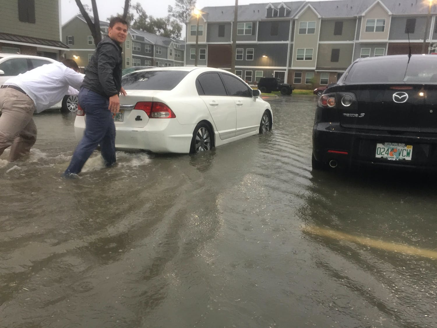 Two men at The Ridge at Gainesville push a car through a flooded parking lot on Tuesday.