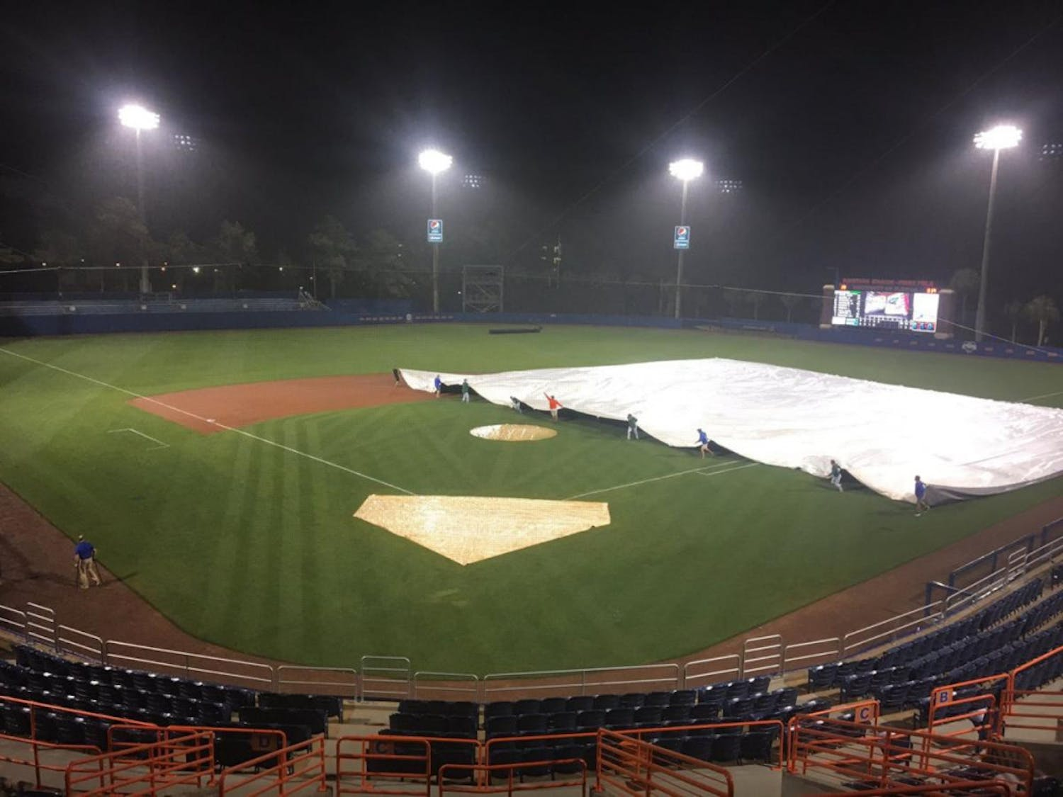 The grounds crew at McKethan Stadium pulls a tarp over the field during a rain delay on April 4, 2017.