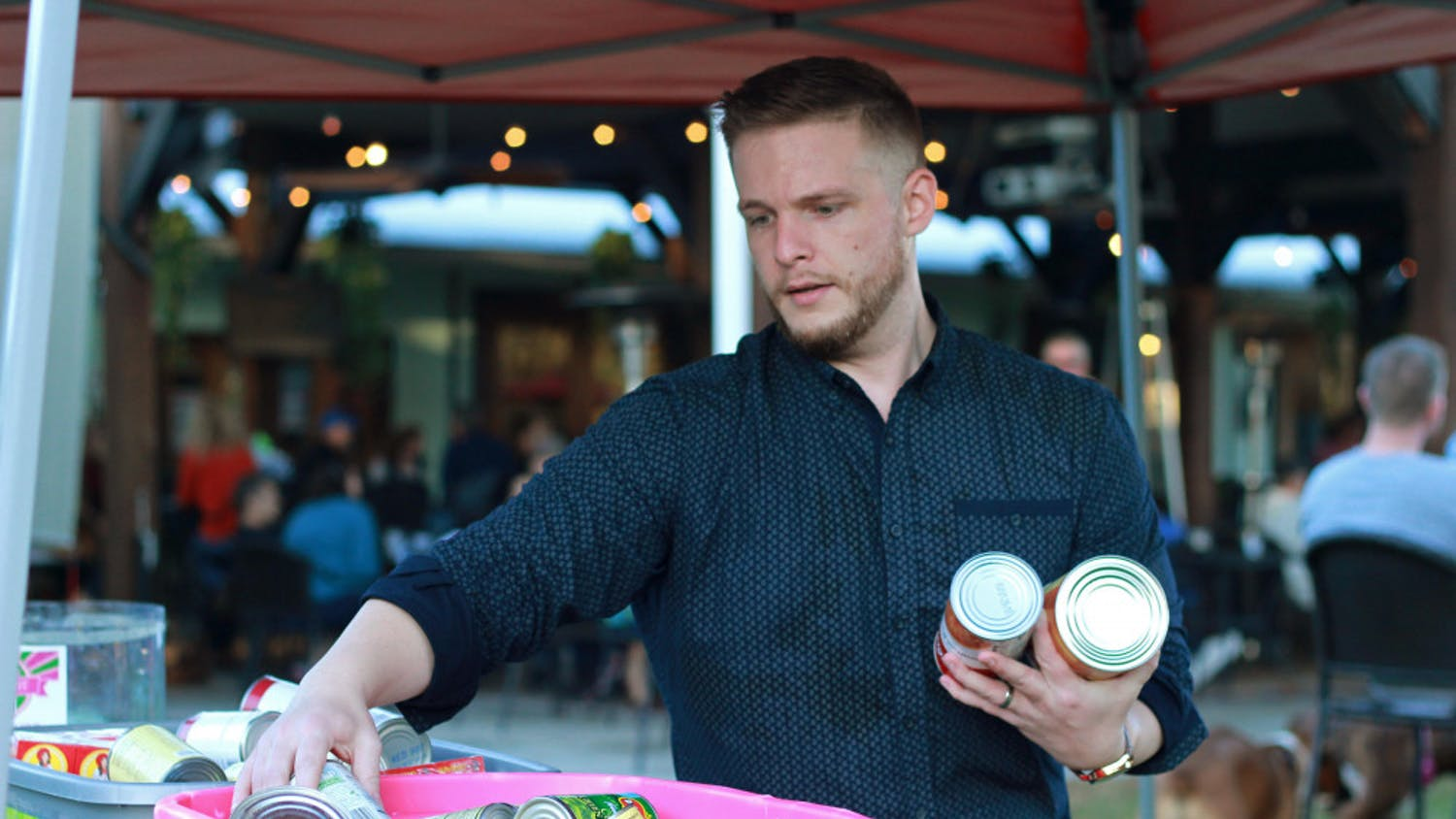 Fundraising organizer Andrew Poe, 28, consolidates donations of canned food Sunday at a food truck rally. Donated food will be given to Bread of the Mighty Food Bank.