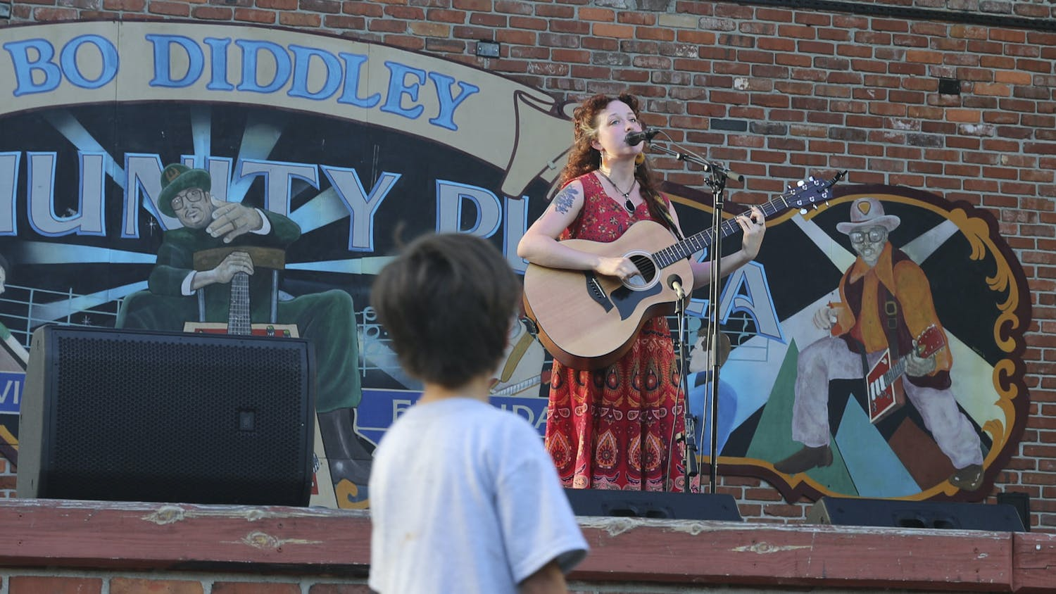 A boy look up at Sara Donnachie, also known as Pose Norma, a Santa Fe music theory student, singing on stage at Bo Diddley Plaza in Gainesville on Thursday, July 15, 2021.