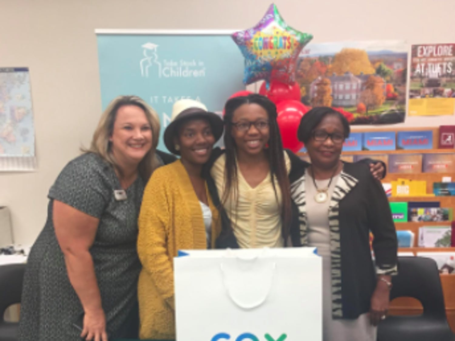 Former Superintendent Karen Clarke, left, Moore's mom, Tedreyonce' Moore and Deputy Superintendent Donna Jones smile on Oct. 28, 2019, the day Moore received her laptop. Clarke and Jones were Moore's mentors. (Courtesy of The Education Foundation of Alachua County)