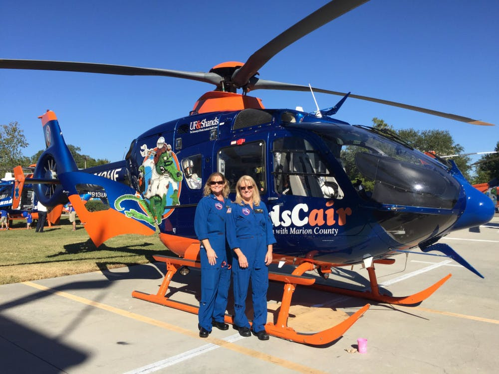 """<p dir=""""ltr"""">ShandsCair 2, an EC13-model helicopter, sits in the sun during the 35th anniversary celebration of UF Health's ShandsCair on Saturday. It is just one of three helicopters used to transport patients from the scene to the UF Health Shands Hospital, a level-one trauma center.</p>"""