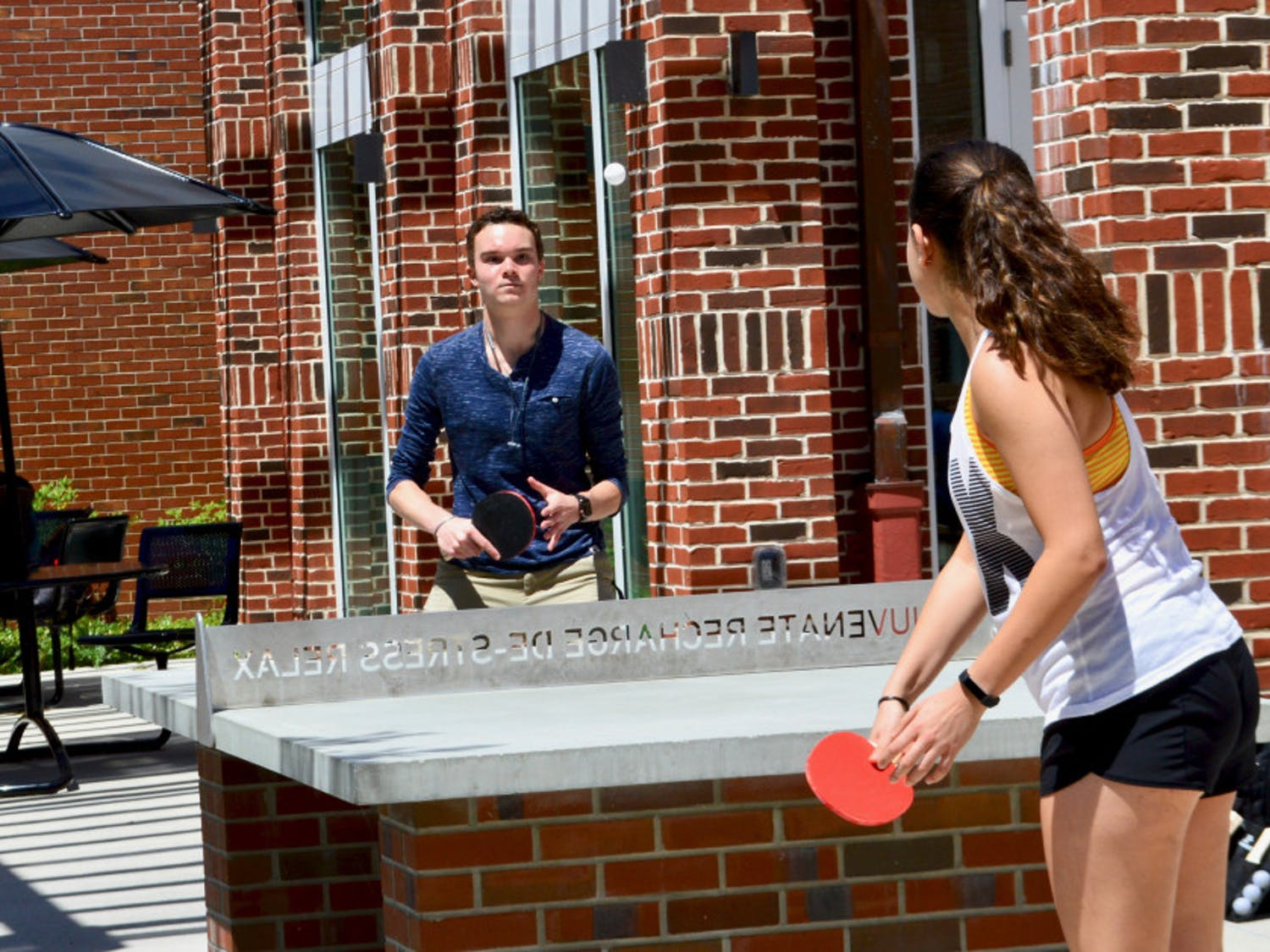 Andrew Schuffer, an 18-year-old neurobiological sciences freshman, plays ping pong outside Newell Hall Tuesday afternoon with Ariana Johnson, a 19-year-old microbiology and cell science freshman as part of the Newell Hall Block Party which marked the one year anniversary of the building's reopening.