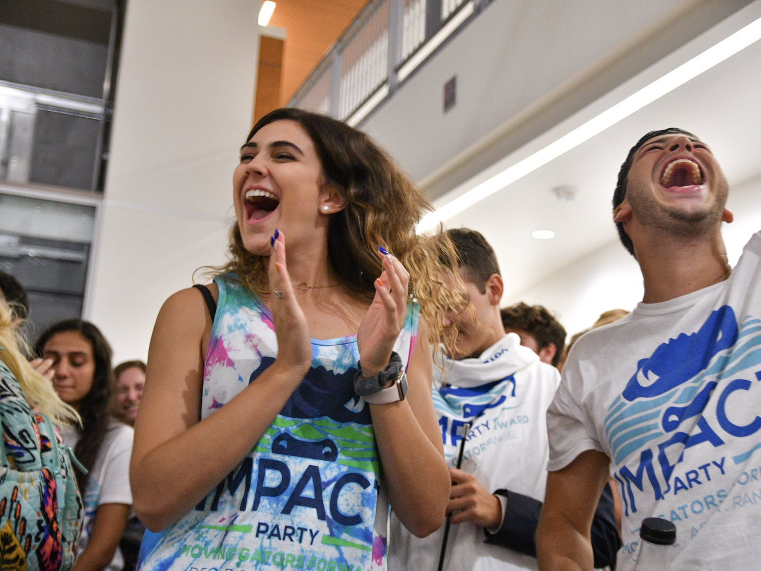 Lexie Atlas, a 19-year-old UF sophomore engineering student, celebrates with her friend Kyle Levy, who just won a District B Senator seat for the Impact Party. The results were read in the Reitz Union Wednesday night where Impact won 35 of 50 seats.