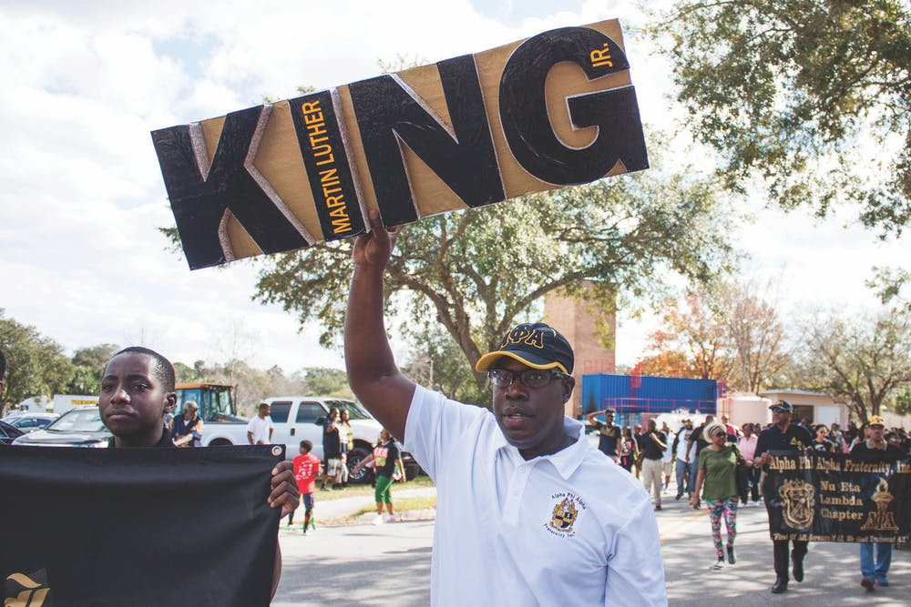 """<p><span id=""""docs-internal-guid-c18bda2f-aaa2-0497-6dda-853de125e0c0""""><span>Maurice Spence, the president of the Alpha Phi Alpha fraternity Gainesville chapter, holds a Martin Luther King Jr. sign during a march on Monday. """"We are instrumental as leaders for the civil rights movement,"""" Spence said about the fraternity. """"We support Dr. King's efforts on a local and national level.""""</span></span></p>"""