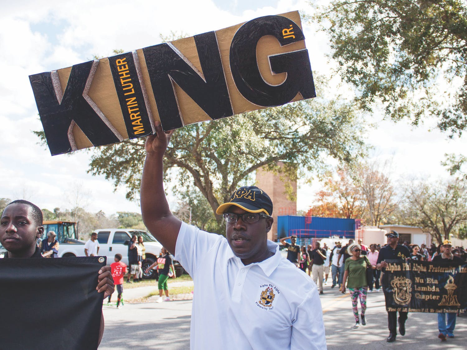 "Maurice Spence, the president of the Alpha Phi Alpha fraternity Gainesville chapter, holds a Martin Luther King Jr. sign during a march on Monday. ""We are instrumental as leaders for the civil rights movement,"" Spence said about the fraternity. ""We support Dr. King's efforts on a local and national level."""