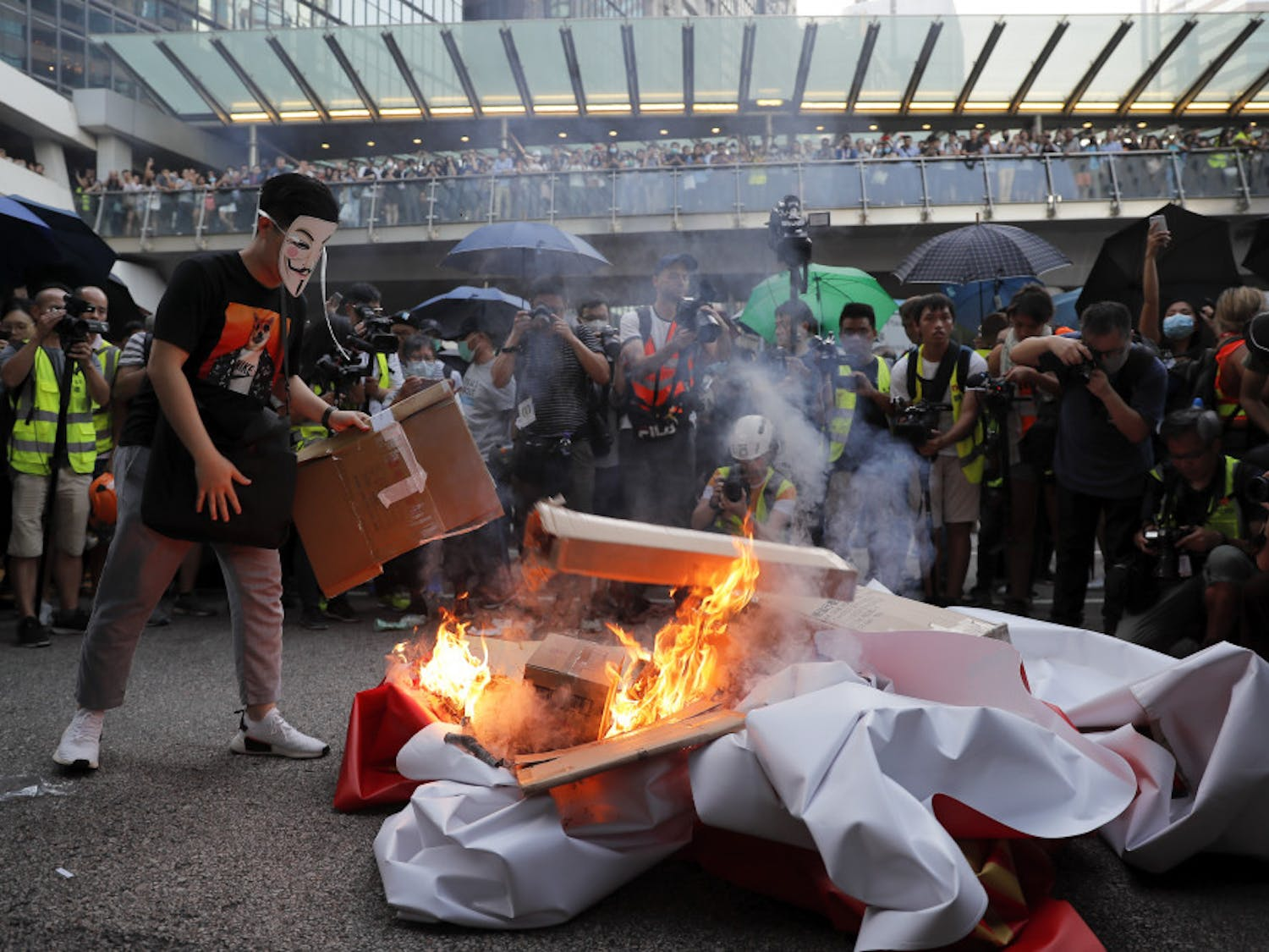 A masked protester sets fire to a China 70th anniversary celebration banner in Hong Kong, Friday, Oct. 4, 2019. Hong Kong Chief Executive Carrie Lam announced that protesters are banned from wearing masks to conceal their identities in a hardening of the government's stance against the 4-month-old demonstrations. (AP Photo/Kin Cheung)
