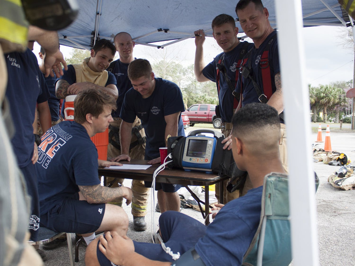 The new hires check each other's vital signs before heading into burning shipping containers for live-burn training at Gainesville Fire Rescue Station 3, located at 900 NE Waldo Rd.