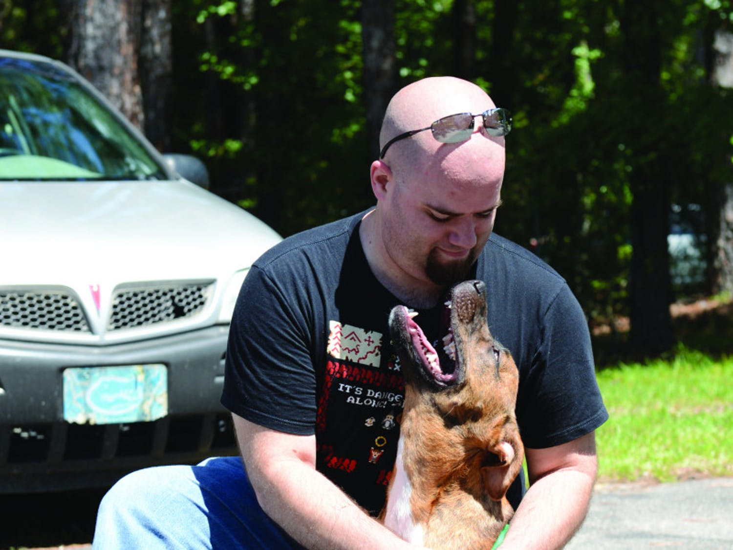 Tim Forbes, 29, puts a leash on his new dog, Graham, at the Summer Lovin' Adoptathon on Saturday. The event found a new home for more than 180 cats and dogs.