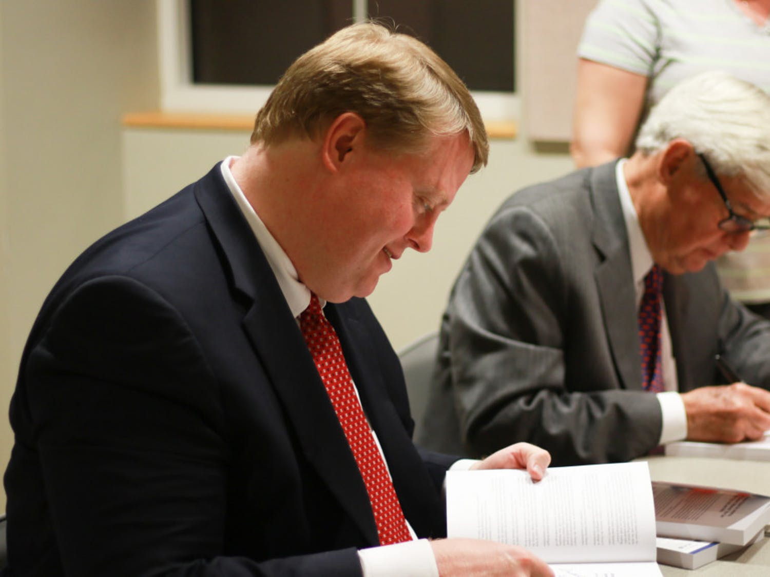"""Chris Hand, a UF alumnus and attorney, signs copies of the second edition of """"America, the Owner's Manual: Making Government Work For You,"""" with the book's co-author, former Florida Gov. Bob Graham."""