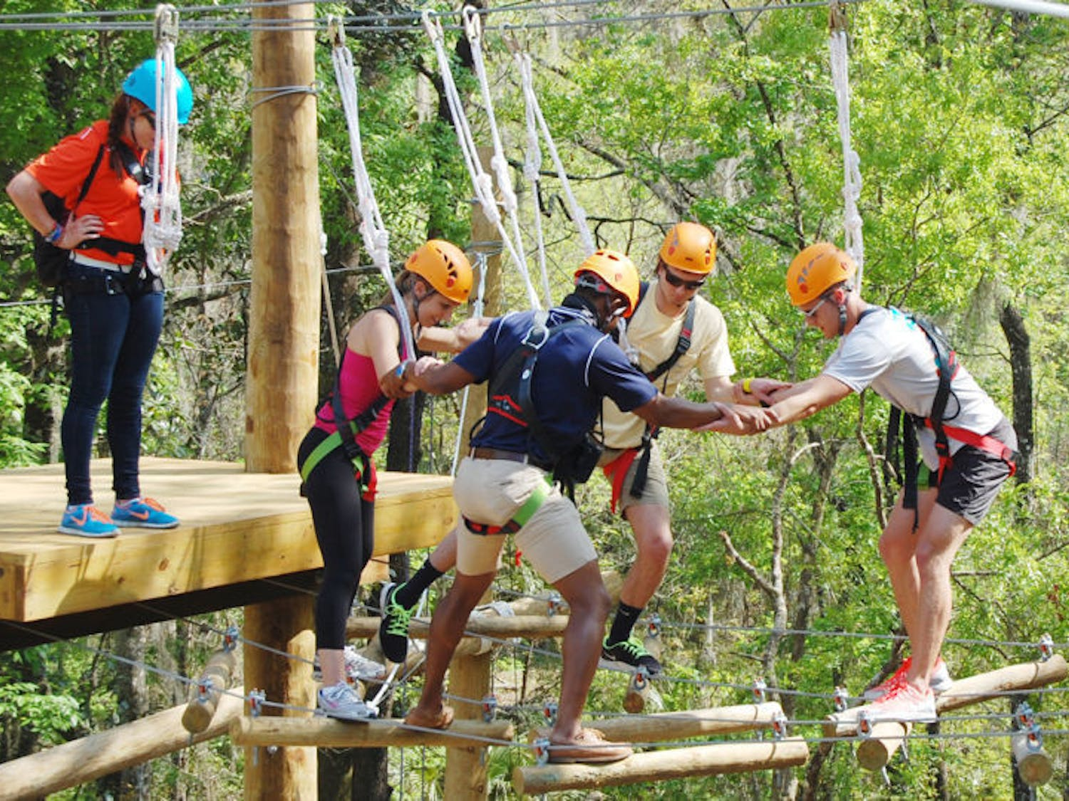 A group makes its way across the top level of the new UF Outdoor Team Challenge Courses at Lake Wauburg on Friday. About 20 people strapped on harnesses to climb to the top and zip line to the bottom.