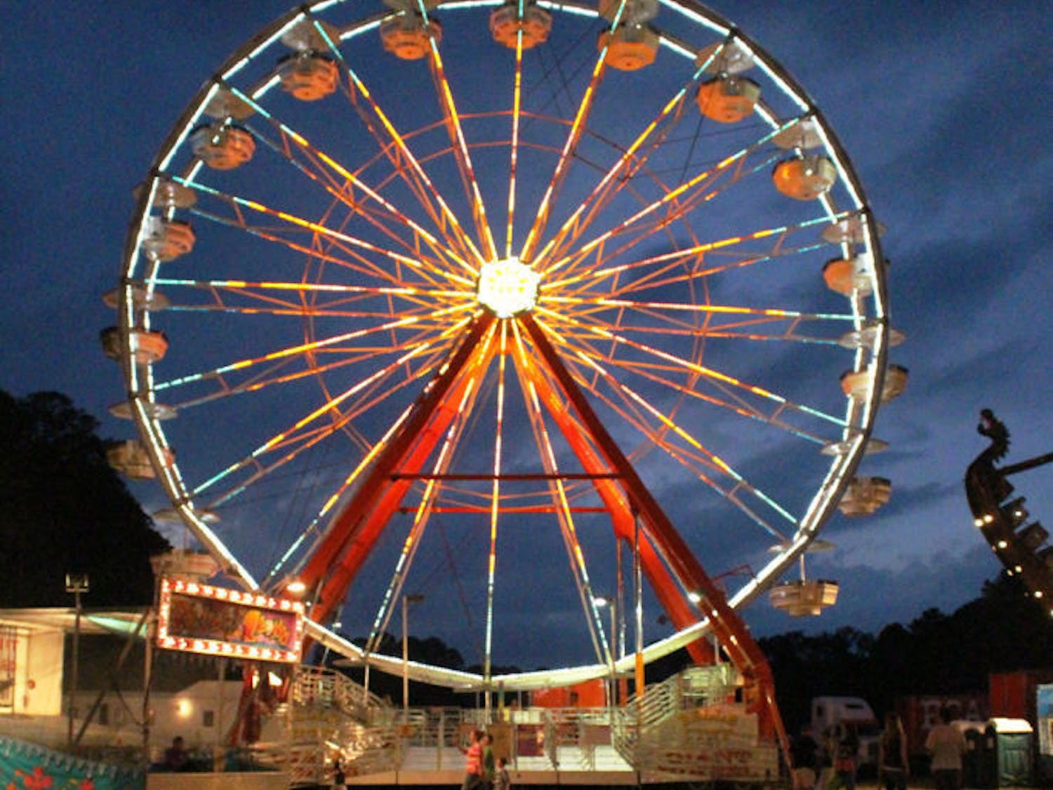 Patrons walk in front of a Ferris wheel Monday evening at the Alachua County Fair, held at the Alachua County Fairgrounds, 3100 NE 39th Ave. The fair runs through Saturday.
