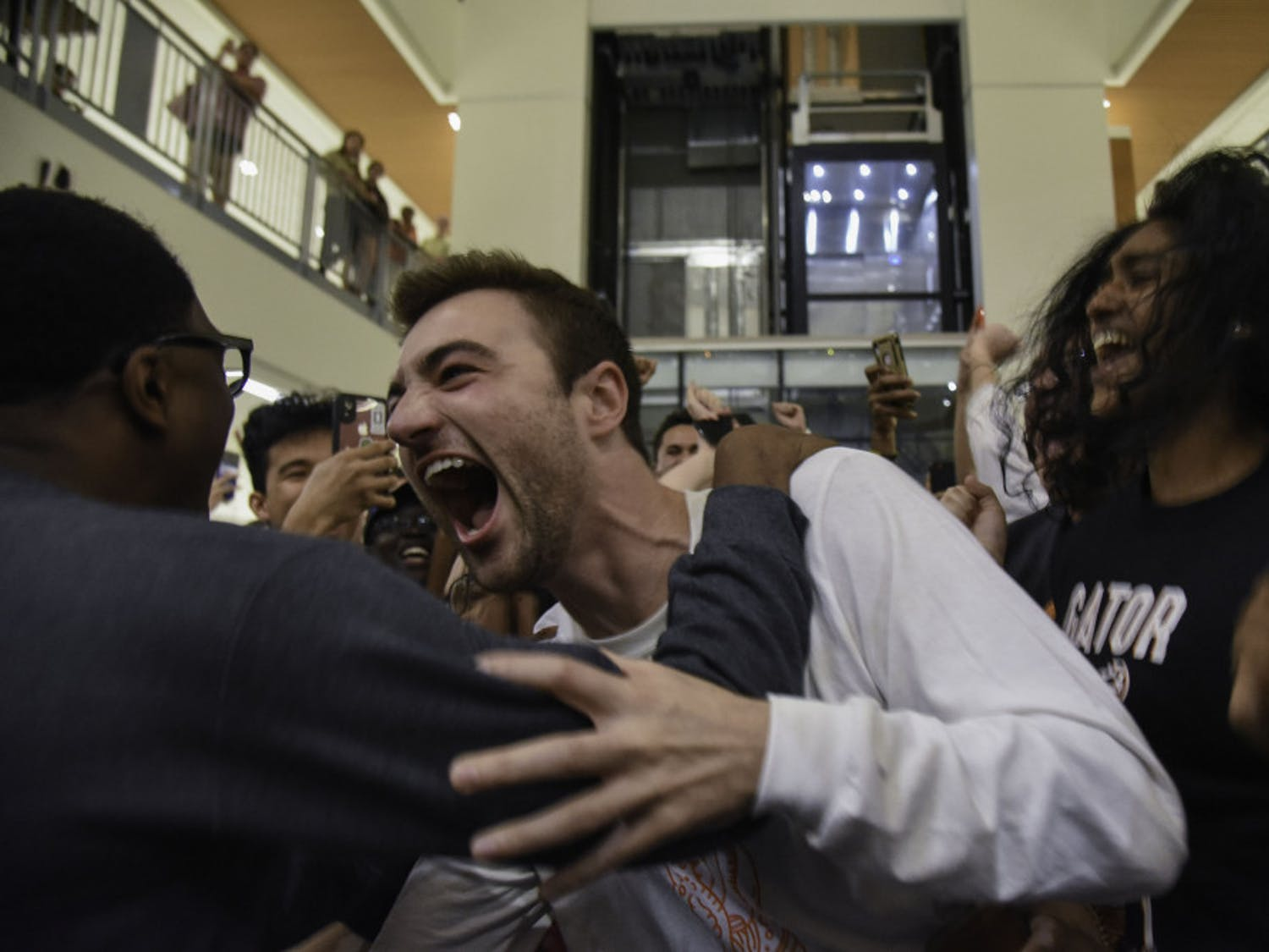 Trevor Pope, a 22-year-old UF law student and the UF Student Government president-elect, grabs ahold of Lauredan Official, a 21-year-old UF advertising junior and the vice president-elect, after finding out election results that were announced at the Reitz Union Wednesday night.