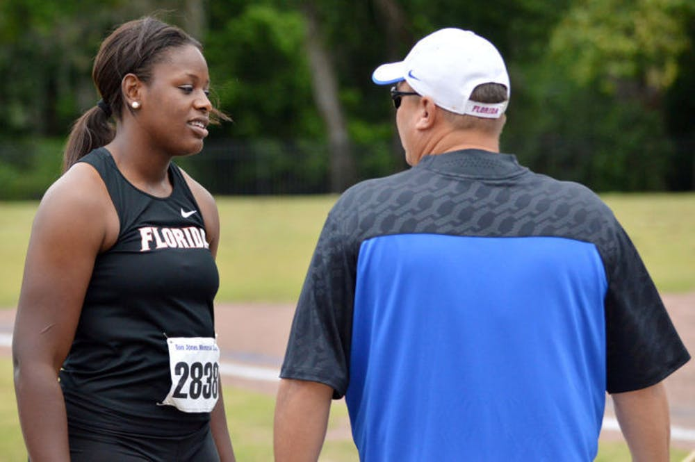 <p>Jayla Bostic talks with throws coach Steve Lemke after one of her hammer throw attempts during the Tom Jones Memorial Invite on April 19, 2014, at Percy Beard Track.</p>