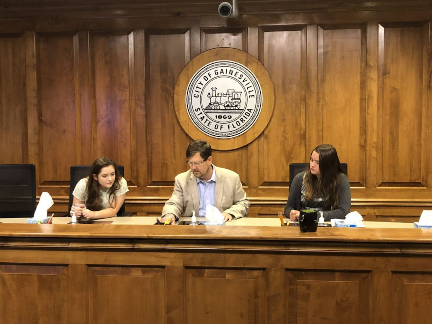 Mayor Lauren Poe (middle) allowed Keelyn Fife (left) and Alissa Humphrey (right) to sit in the city commission chairs while watching their peers' presentation.
