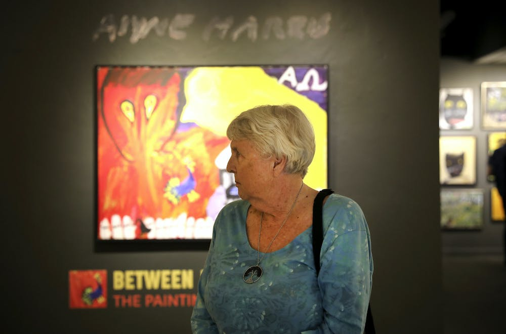 """Nancy Parkinson, 80, a Gainesville resident, stands in front of artwork at the """"Between Heaven and Earth"""" exhibit at the Historic Thomas Center on Thursday, June 17, 2021."""