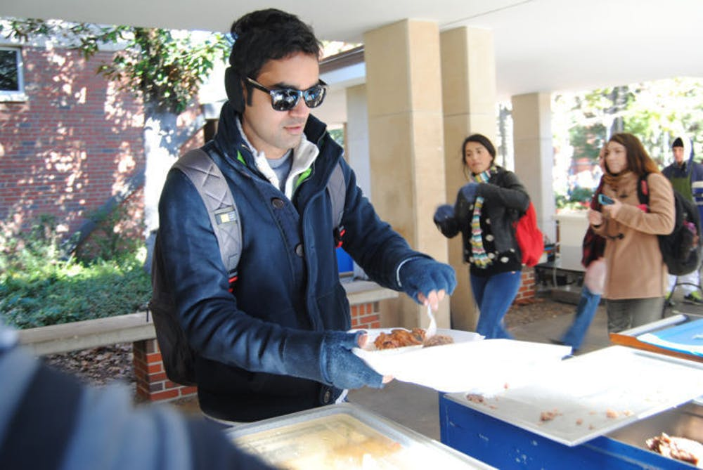 """<p class=""""p1""""><span class=""""s1"""">During his lunch hour, 26-year-old UF chemical engineering doctoral student Virat Upadhyay serves himself Krishna Lunch using their new to-go containers. Krishna staff has started using the containers in order to help keep food servings — and customers — warm.</span></p>"""