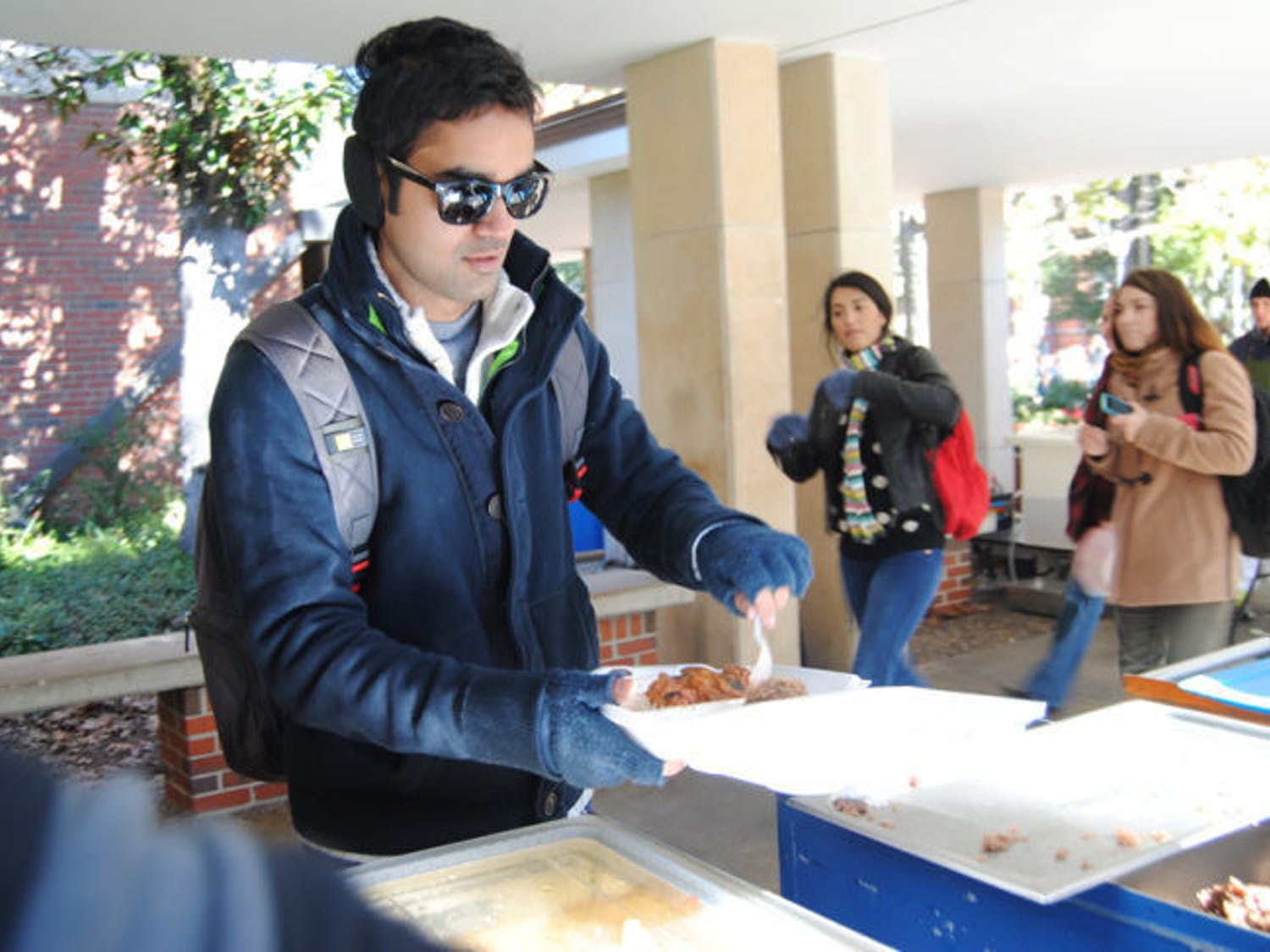 During his lunch hour, 26-year-old UF chemical engineering doctoral student Virat Upadhyay serves himself Krishna Lunch using their new to-go containers. Krishna staff has started using the containers in order to help keep food servings — and customers — warm.