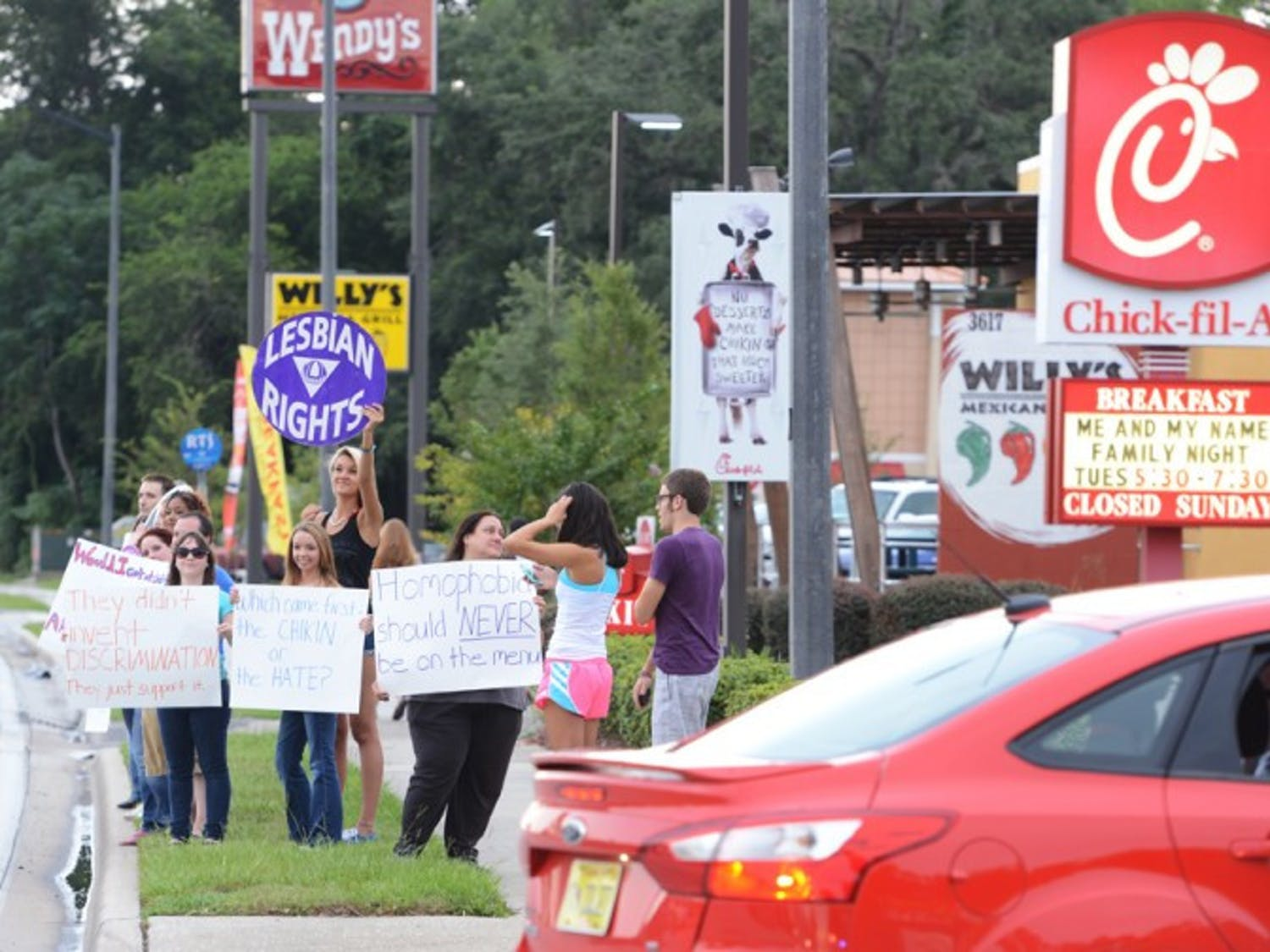 Protesters supporting gay rights stand along Southwest Archer Road in front of Chick-fil-A. Thousands of people flocked to Chick-fil-A to support the restaurant chain's traditional stance on marriage rights.