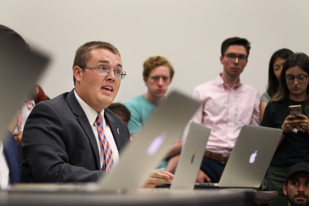 "<p dir=""ltr""><span>Branden Pearson speaks in defense of Gator Party against allegations of campaign violations Thursday evening at a Student Government Elections Commission meeting at the Levin College of Law. The meeting followed a contentious Senate race between Gator Party and Inspire Party.</span></p><p><span> </span></p>"