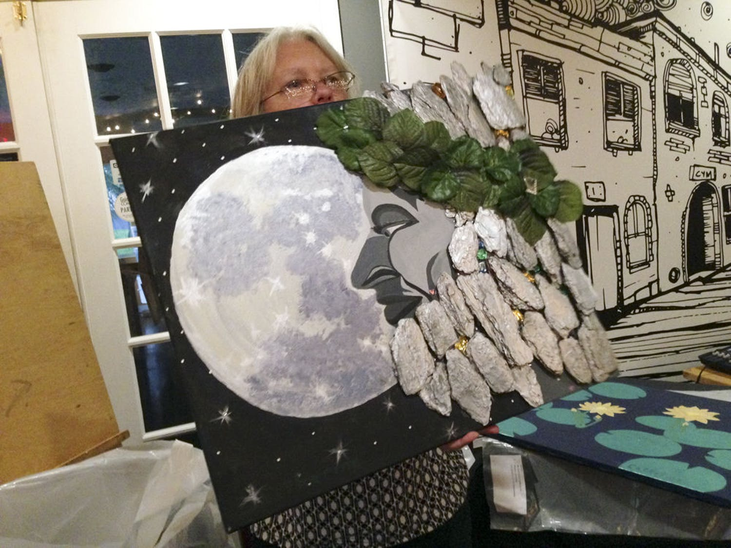 """Event coordinator Maggie Hannon displays """"Father Time,"""" a mixed-media piece by Catherine Kennedy, at the Reframing Recovery artisan exhibit for artists overcoming mental illness Saturday at Cymplify."""