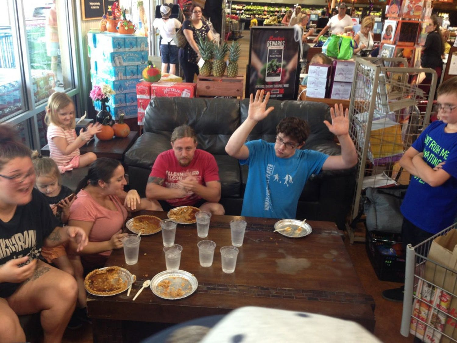 Steven Edvalson raises his hands in victory after finishing his pumpkin pie on Sunday at Lucky's Market. Edvalson ate his pie in fewer than seven minutes during a pie-eating contest at the grocery store.