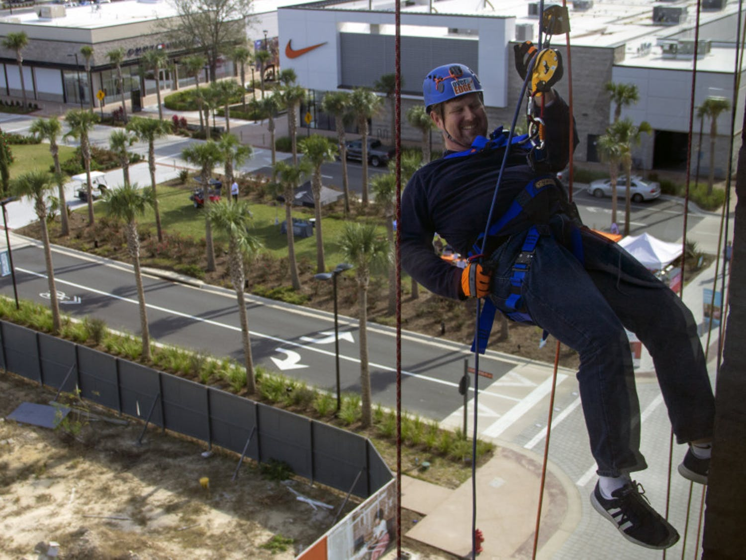 """Gainesville Mayor Lauren Poe descends down the side of the 5001 building in Celebration Pointe Friday during the Alachua Habitat for Humanity's Over the Edge fundraiser. The fundraiser raised at least $15,000 for the organization. """"You just lean back and enjoy the ride,"""" Poe said."""