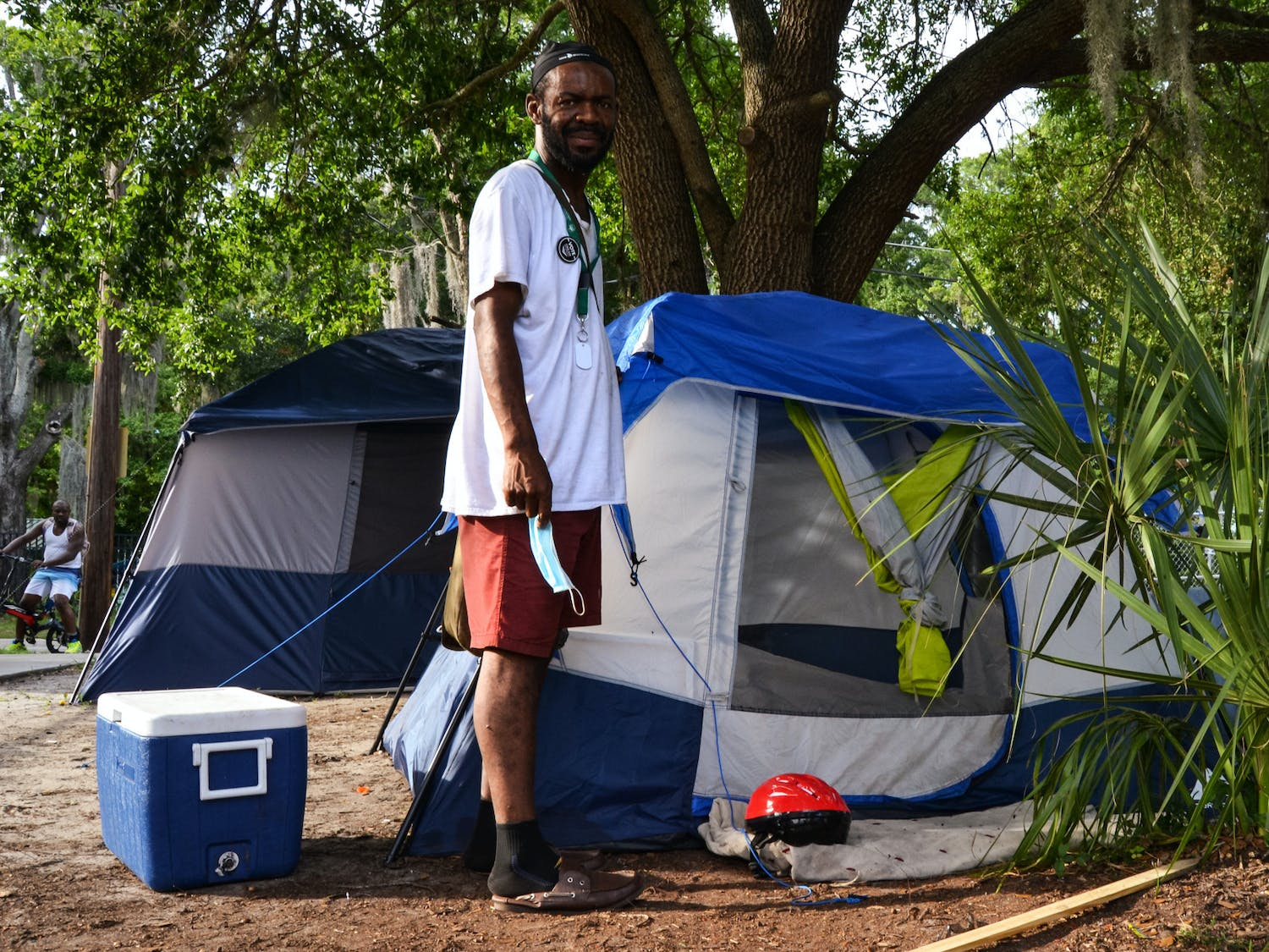 """Robert Thomas, 43, stands in front of his tent behind the old fire station in downtown Gainesville where he says it's """"more peaceful"""" on Thursday, June 10, 2021. Thomas doesn't know what he'll do if the SPARC arts center is built, but says he's willing to fight for the people camped out on the property."""