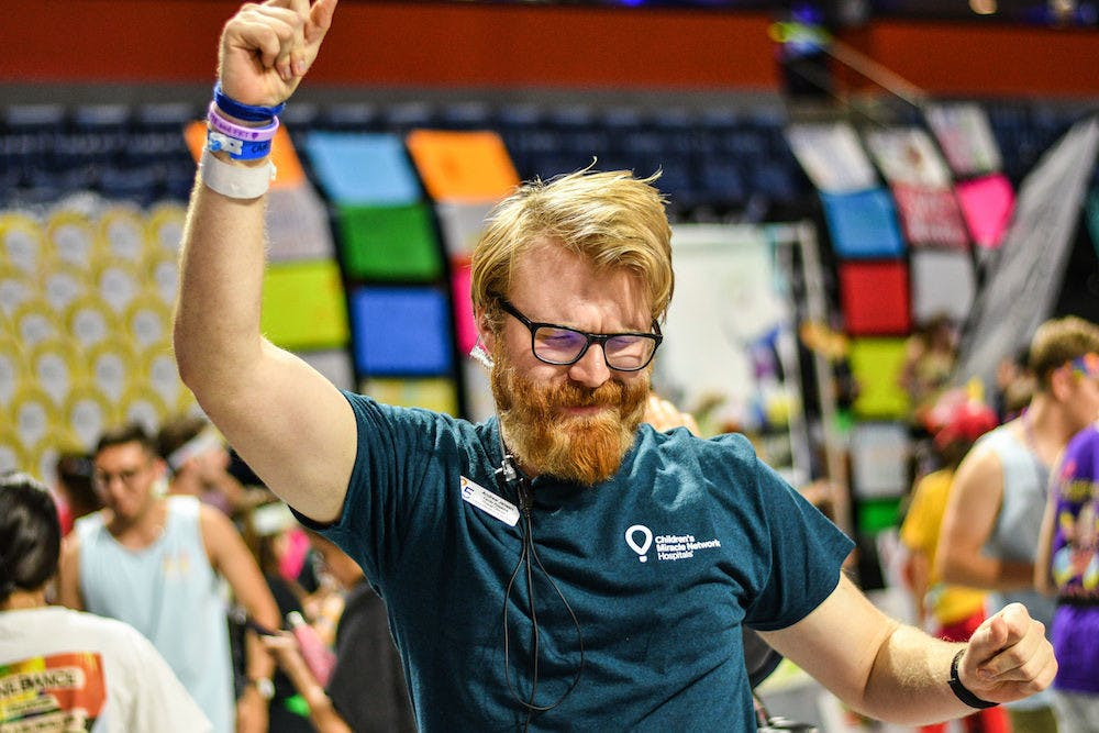 """<p dir=""""ltr""""><span>Andrew Jensen, the Overall Director of Dance Marathon 2019, rocks out during the Savants of Soul's performance Saturday night in the O'Connell Center. Dance Marathon lasted for 26.2 hours and raised $3,230,025.23 for children at</span> <span>UF Health Shands Children's Hospital and Children's Miracle Network.</span></p>"""