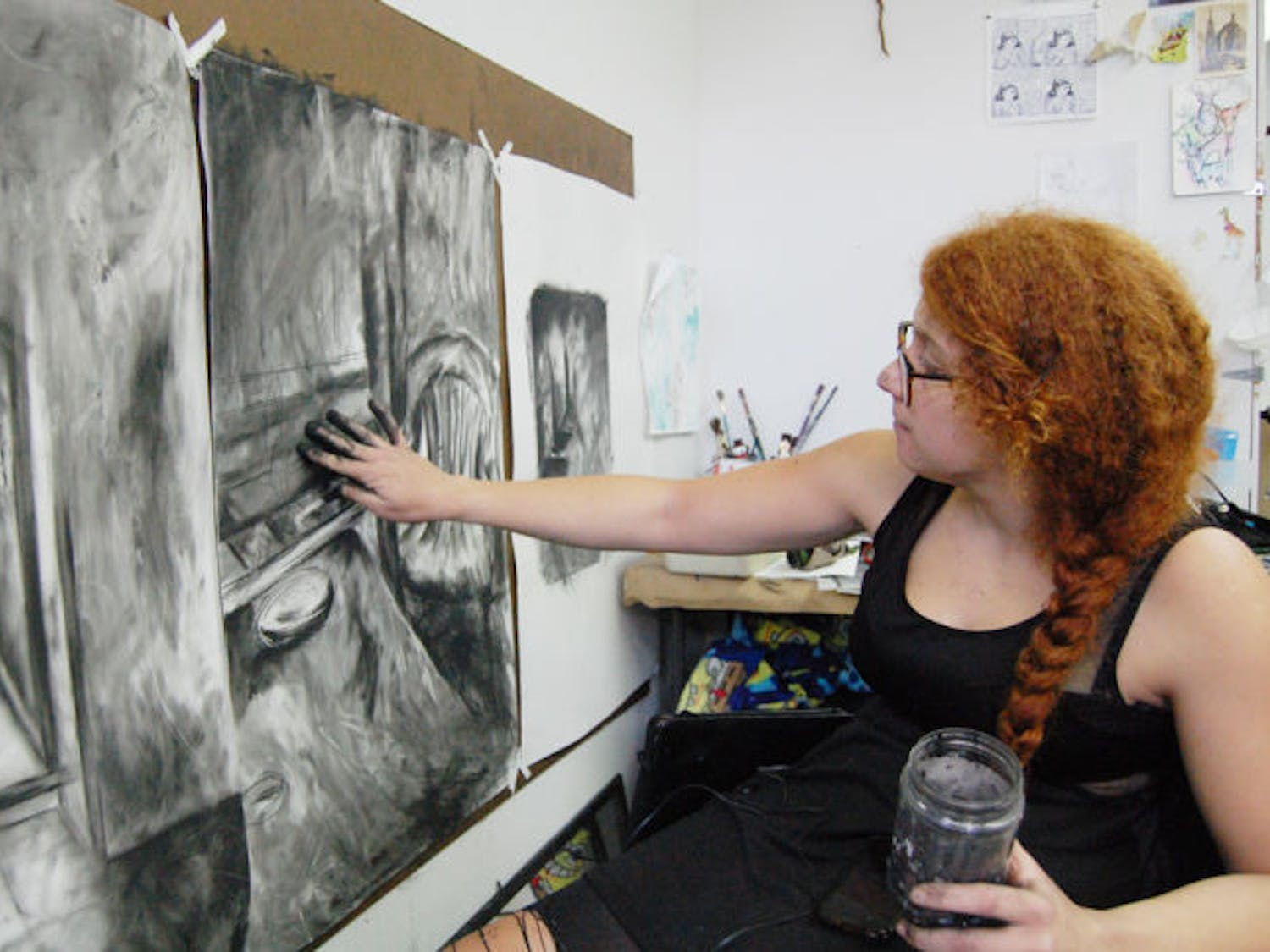 Dounia Bendris, a 21-year-old UF drawing senior, doesn't like hard lines in her work, so she uses her fingers to smear her charcoal drawings. With black-stained hands, her fingerprints create a shadow and light effect. She dips her fingers into a water jug to seal the charcoal when she's satisfied with an area.