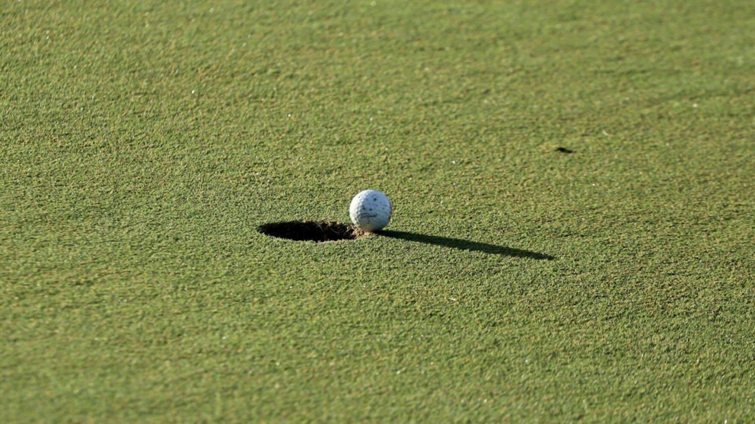 A ball hangs over the hole at Mark Bostick Golf Course