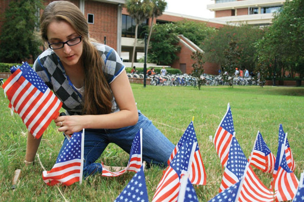 <p>Graduate student Jean Morrow places exactly 2,977 miniature flags on the lawn of the Reitz Union lawn to honor each person who died on 9/11, marking the 10th anniversary of the national tragedy. Morrow's display is part of the 9/11: Never Forget Project at UF.</p>