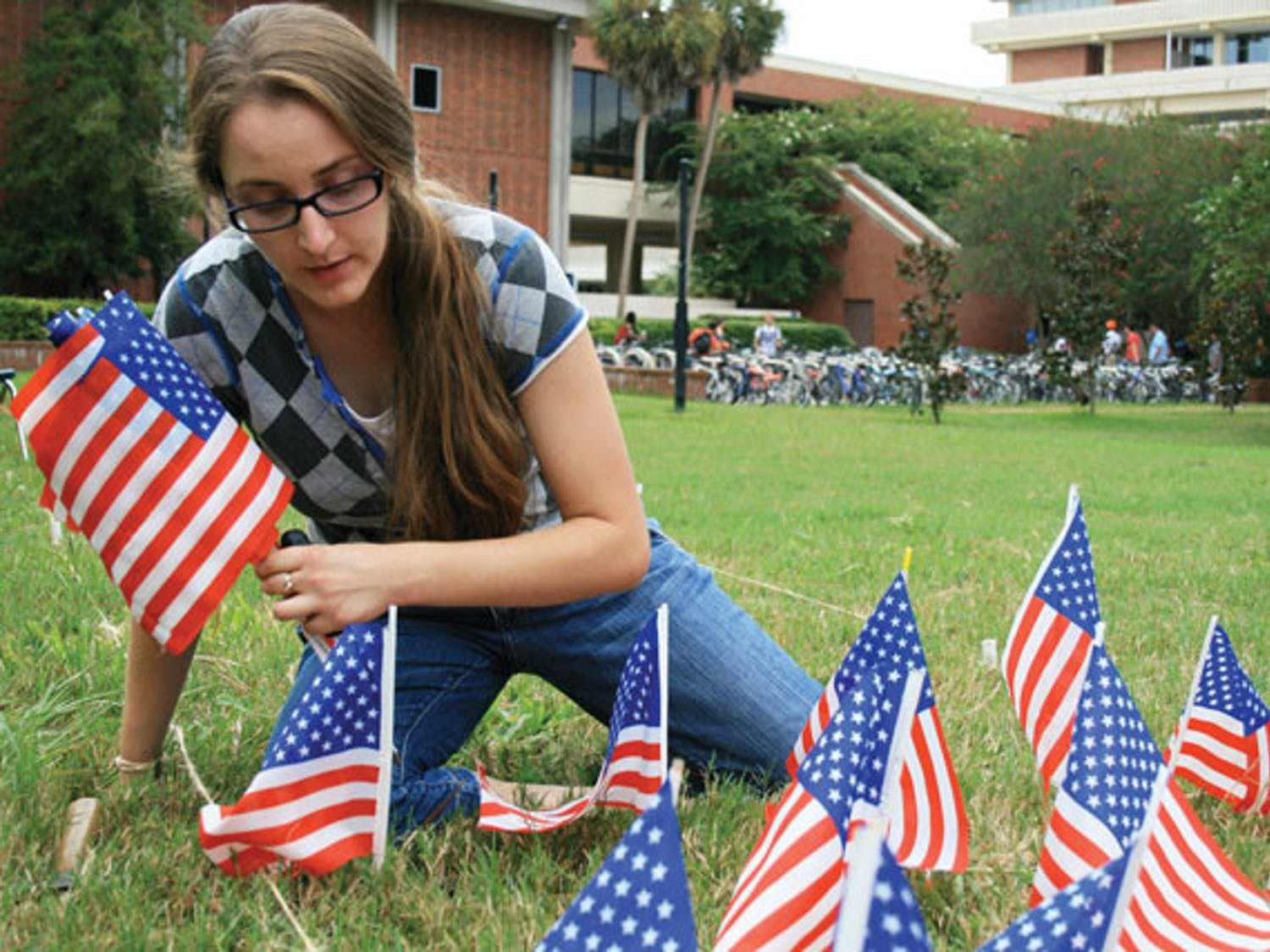 Graduate student Jean Morrow places exactly 2,977 miniature flags on the lawn of the Reitz Union lawn to honor each person who died on 9/11, marking the 10th anniversary of the national tragedy. Morrow's display is part of the 9/11: Never Forget Project at UF.