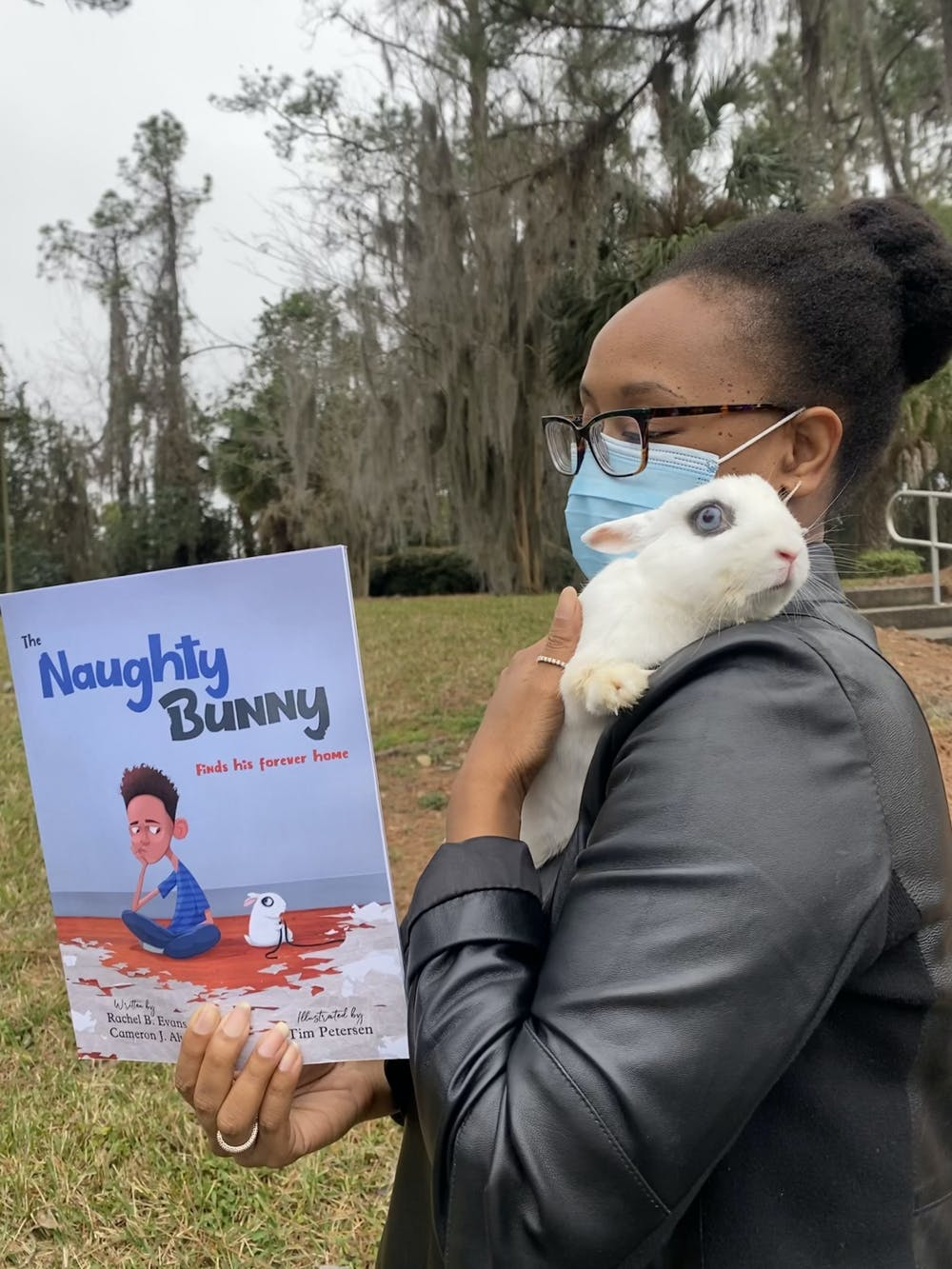 Rachel Evans holds pet rabbit Tiny and the book she co-authored with her son, Cameron Alvarado, about their journey with the pet.