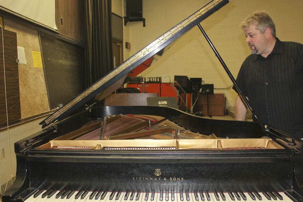 <p>Trent Wellers, the building manager for UF's School of Music, checks whether a piano's strings are swollen to see if it needs tuning. The piano is about 70 years old.</p>